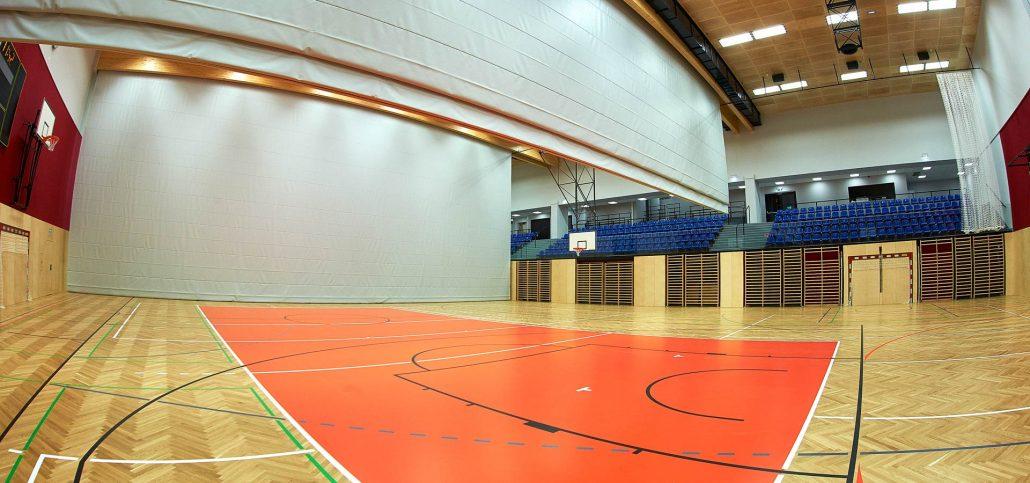 Sporthalle mit Basketballfeld und hochgezogener Trennwand